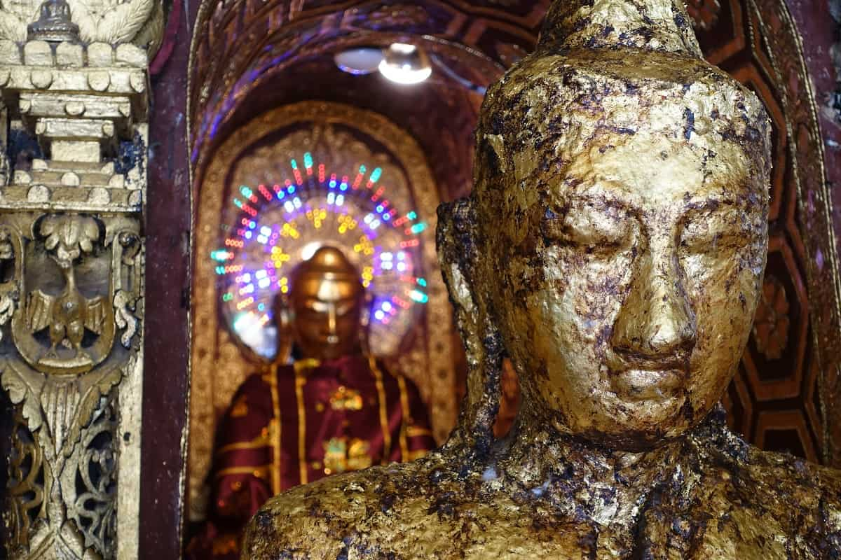 Closeup - gold-leaf encrusted Buddha at the Kawnagammana Buddha shrine