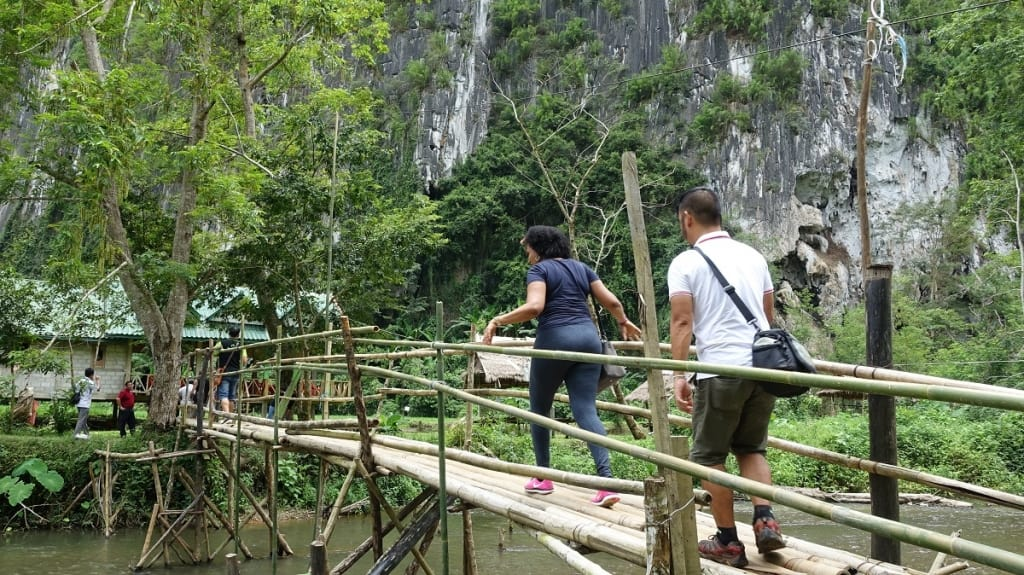 Tourists crossing a bridge in the Lao countryside.